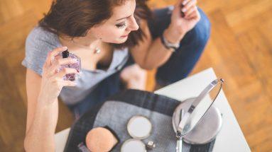 Parfüm richtig auftragen: Frau sprüht sich mit Parfüm ein