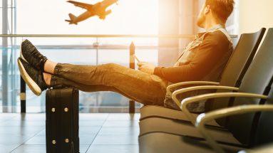 Parfum im Handgepäck: Passagier wartet in Abflughalle mit Gepäck